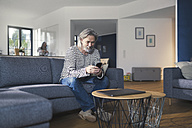 Senior man sitting on couch, using smartphone - SBOF00464