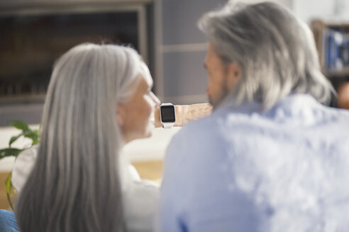 Senior couple looking at smartwatch - SBOF00482