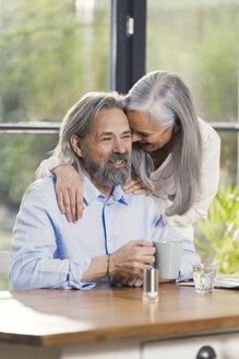 Happy senior couple drinking coffee at home - SBOF00491