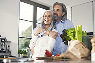 Happy senior couple preparing food in kitchen - SBOF00497