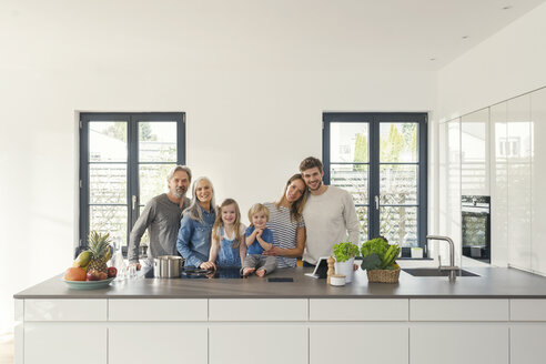 Happy family with grandparents and children standing in the kitchen - SBOF00509