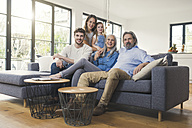 Extended family sitting on couch, smiling happily - SBOF00521