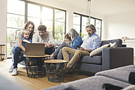 Extended family sitting on couch, using mobile devices - SBOF00524