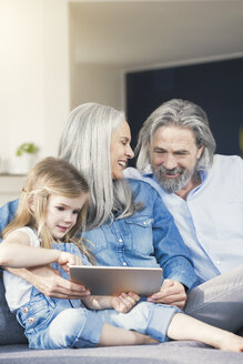 Grandparents and granddaughter sitting on couch, using tablet - SBOF00527
