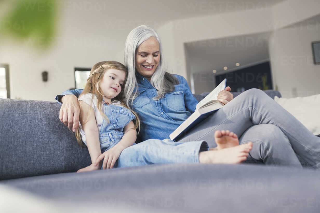 Grandmother and granddaughter sitting on couch, reading together - SBOF00533 - Steve Brookland/Westend61