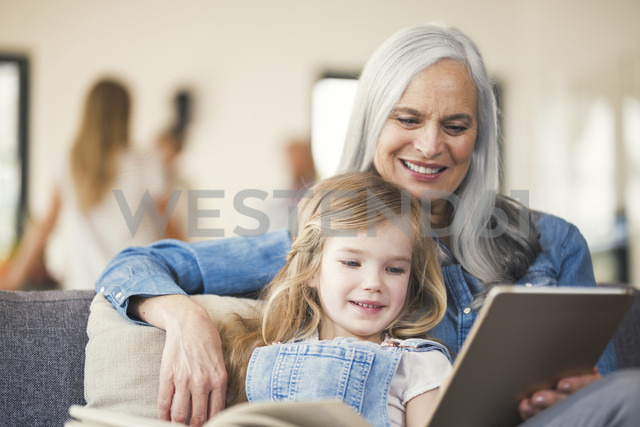 Grandmother and granddaughter sitting on couch, reading together - SBOF00536 - Steve Brookland/Westend61
