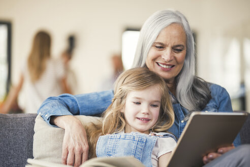 Grandmother and granddaughter sitting on couch, reading together - SBOF00536