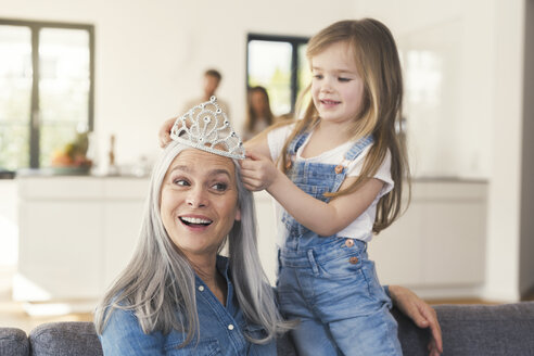 Granddaughter putting crown on grandmothes head - SBOF00539