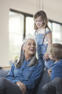 Grandmother wearing crown, sitting on couch with grandchildren - SBOF00542