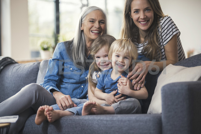 Grandmother and mother sitting on couch with children - SBOF00545