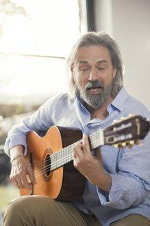 Senior man playing passionately his guitar - SBOF00548