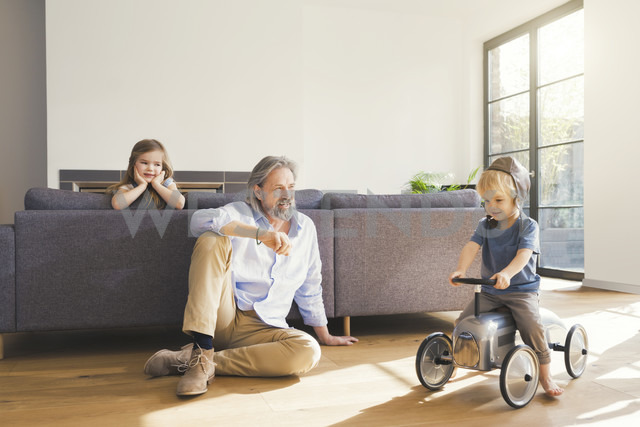 Grandfather playing with grandchildren, sitting on toy car - SBOF00554 - Steve Brookland/Westend61