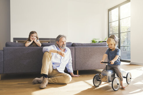 Grandfather playing with grandchildren, sitting on toy car - SBOF00554