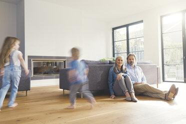 Grandparents observing grandchildren, playing in livingroom - SBOF00560