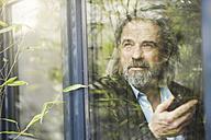 Senior businessman standing by window, using smartphone - SBOF00566