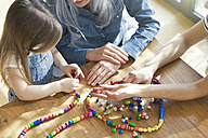 Grandmother and granddaughter and mother threading beads - SBOF00578