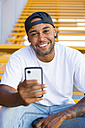 Portrait of smiling young man with smartphone sitting on stairs - MGIF00059