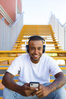 Portrait of laughing young man with headphones and smartphone sitting on stairs - MGIF00062