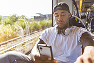Portrait of young man in tramway looking at smartphone - MGIF00068
