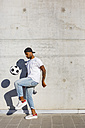 Young man playing with soccer ball in front of concrete wall - MGIF00077