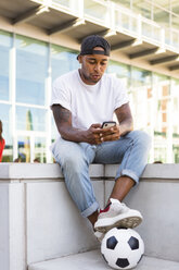 Young man with soccer ball isitting on a wall looking at cell phone - MGIF00080