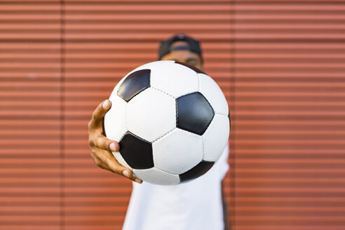 Man's hand holding soccer, close-up - MGIF00083