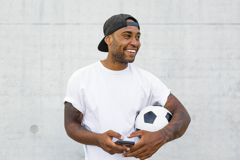 Portrait of laughing young man with soccer ball and cell phone - MGIF00086