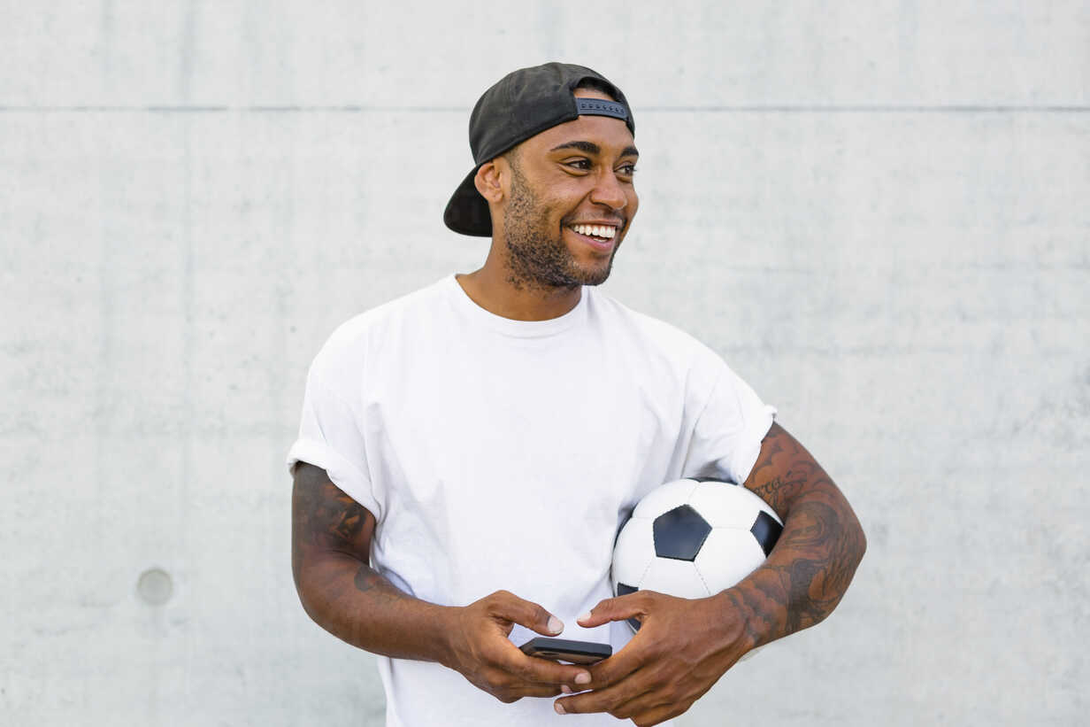 Portrait of laughing young man with soccer ball and cell phone - MGIF00086 - Giorgio Magini/Westend61