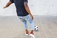 Back view of young man playing with a soccer ball against concrete wall, partial view - MGIF00089