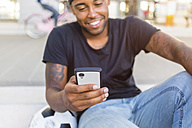 Smiling young man looking at smartphone, close-up - MGIF00092