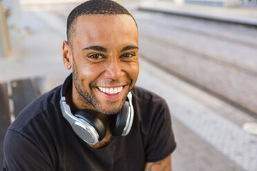 Portrait of laughing young man with headphones waiting at tram stop - MGIF00095