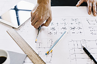 Architect working on construction plan, close-up - GIOF03037