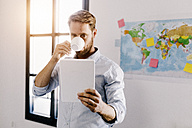 Bearded man in office drinking coffee while looking at tablet - GIOF03040