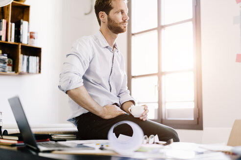 Architect with cup of coffee sitting on desk in his office looking at distance - GIOF03061