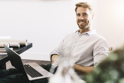 Portrait of smiling architect with laptop in his office - GIOF03067
