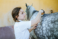 Young woman grooming horse - KIJF01698