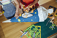 Mother and daughter creating her space themed school cone at home - MFF03706