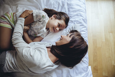 Mother and daughter cuddling on bed - MFF03724