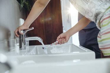 Girl cleaning her tooth brush in bathroom - MFF03736