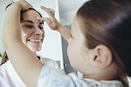 Daughter putting facial cream on mother's face - MFF03739