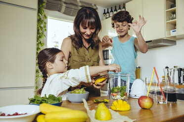 Mother and children putting fruit into a smoothie blender - MFF03751