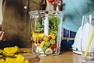 Close-up of mother and children putting fruit into a smoothie blender - MFF03754