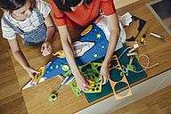 Mother and daughter creating her space themed school cone at home - MFF03772