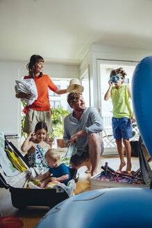 Happy family of five packing for holiday trip - MFF03778