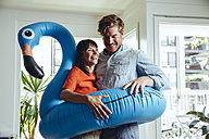 Happy couple holding an inflatable flamingo at home - MFF03781