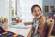 Happy girl doing her schoolwork at home - MFF03784