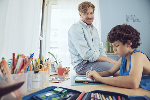 Father helping boy doing his schoolwork at home - MFF03790