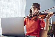 Woman using laptop to play a song on a violin - MFF03793