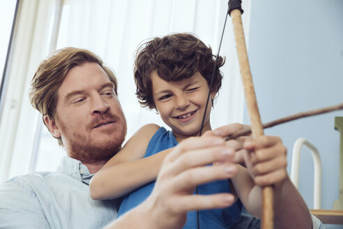 Father showing son how to use self-made bow and arrow - MFF03802