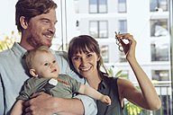 Happy couple with baby holding house key - MFF03811